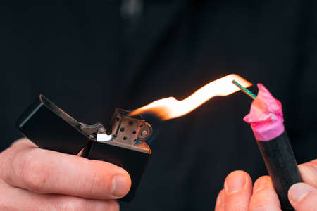 Setting Fire to the Firecracker. Man in Black Clothes Lighting Up the Petard. Firing Up the Pyrotechnics with a Black Gasoline Lighter Outdoors Imagens