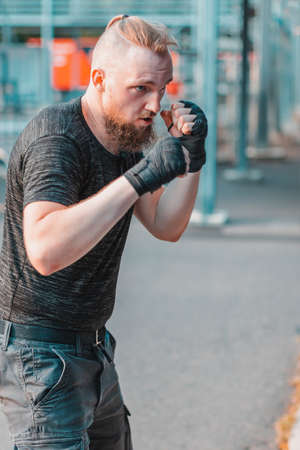 Street Fighter in Black Clothes and Bandages on the Wrist Boxing in Punching Bag Outdoors. Young Man Doing Box Training and Practicing His Punches at the Outside Gym Zdjęcie Seryjne