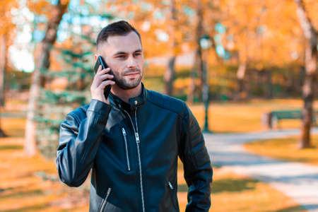 Handsome Young Man Talking on the Phone at the Beautiful Autumn Park. Youthful Guy Using Smartphone for the Call Outdoors at Sunny Day Stock fotó