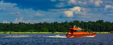 Orange pilot boat moving by the river in Europe. Rescue service