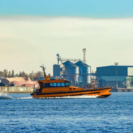 Orange pilot ship sailing past the factory in Latvia