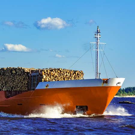 Orange bulk carrier sailing in clear summer day