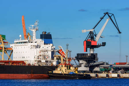Black cargo ship mooring at the port with tug ship support
