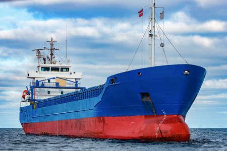 Blue cargo ship moored in still Baltic sea water