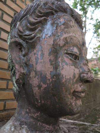 cabeza de buda: Cabeza de Buda en frente de la pared.
