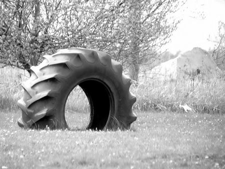 A Huge Tire, half buried in the ground for kids to play on and in Stok Fotoğraf
