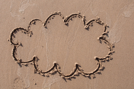 coastal: A speech cloud or think bubble drawn out on a sandy beach. Beach background. Top view
