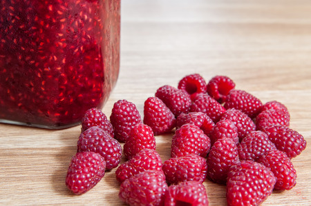 Raspberry jam in jar isolated on a wooden table