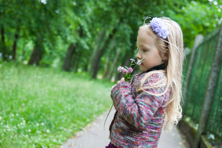 little beautiful girl with long blond hair is smelling flowers in nature Stock Photo