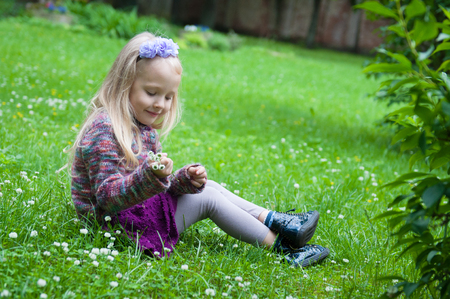 little beautiful girl with long blond hair with flowers on the grass