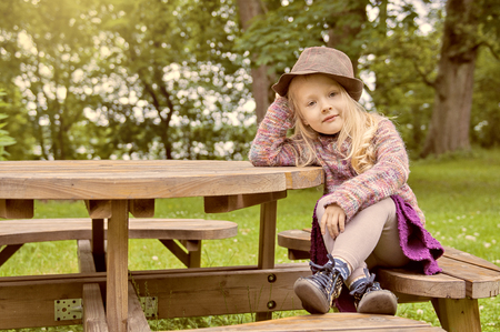 little beautiful girl with long blond hair in the village on a picnic