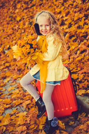 Little girl with blond hair in autumn background with flowers and suitcase