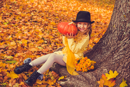 Little beautiful girl with blond hair with big pumpkin in autumn background. Halloween Archivio Fotografico