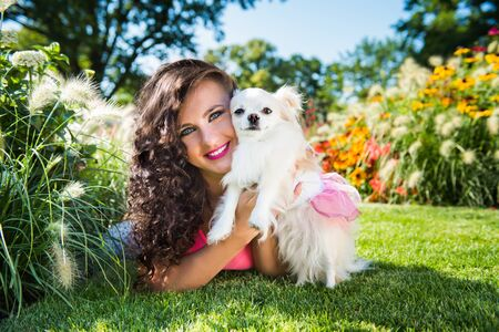 Beautiful girl with a small dog Chihuahua in the park Stockfoto