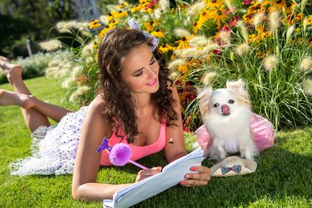 Beautiful girl with a small dog Chihuahua in the park Banco de Imagens