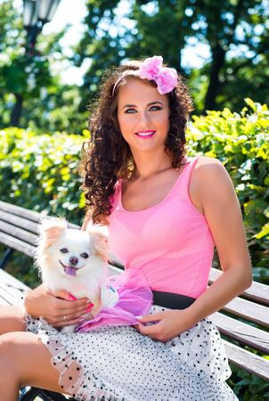Beautiful girl with a small dog Chihuahua in the park Banque d'images