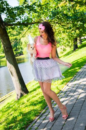Beautiful girl with a small cute dog Chihuahua in the park Stockfoto - 128618233