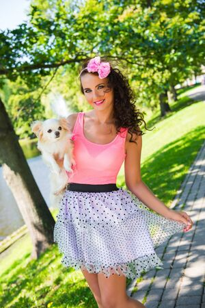 Beautiful girl with a small cute dog Chihuahua in the park