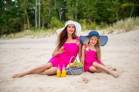 Mom with a daughter on the beach drink juice.