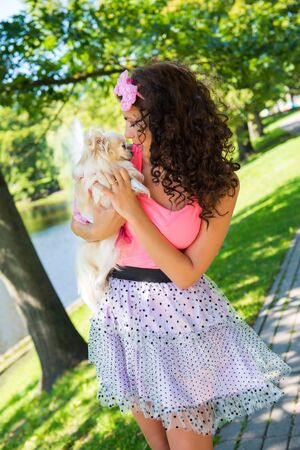 Beautiful girl with a small cute dog Chihuahua in the park Stockfoto - 128609226