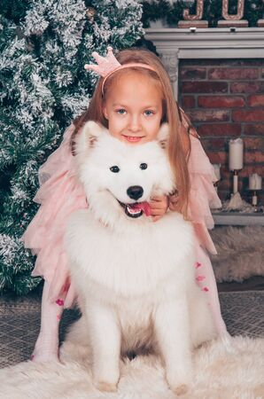 Blonde girl and Samoyed dog by the New Year tree.