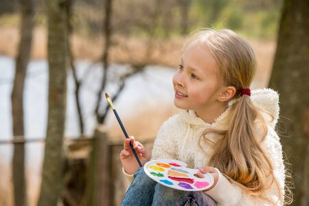 Little girl paints in the spring on nature