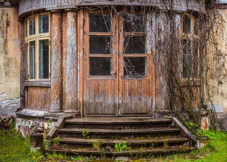 Old brown wooden door with window panes. Old wooden building with weathered doorway Redakční