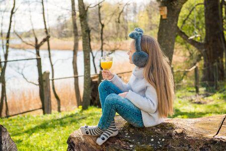 Little girl drinking orange vitamin juice in the morning in the park outdoors in spring. Reklamní fotografie