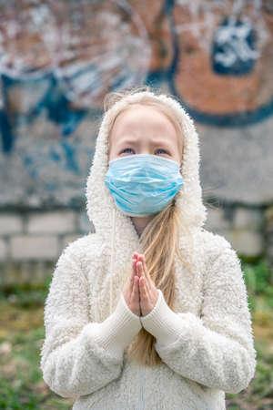 Little child girl wearing respirator mask asks for help for stop coronavirus outbreak, New virus Covid-19. Riga, Latvia, 29.04.2020 Redakční
