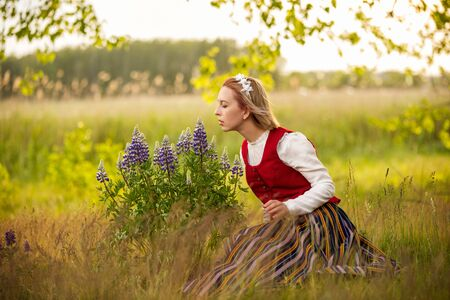 Latvian woman in traditional clothing in field.