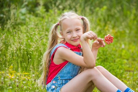 Blonde little girl with long hair and candy on a stick Reklamní fotografie