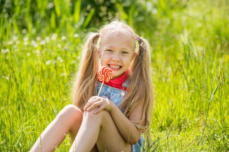 Blondes kleines Mädchen mit langen Haaren und Süßigkeiten am Stiel