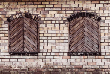 Two windows with closed wooden shutters on a brick