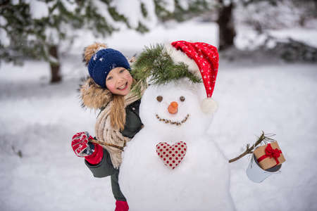 Happy child girl plaing with a snowman on a snowy winter walk