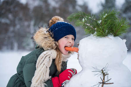 Happy girl child plaing with a snowman on a snowy winter walk 版權商用圖片
