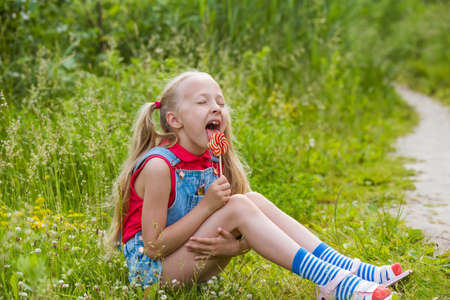 Blonde little girl with long hair and candy on a stick 版權商用圖片