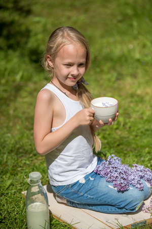 Little girl with cup of milk on nature