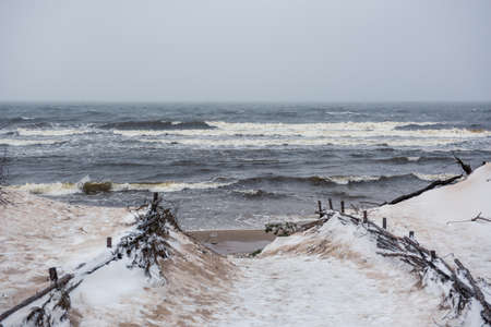 Baltic Sea beach is snowy in winter and there are big waves