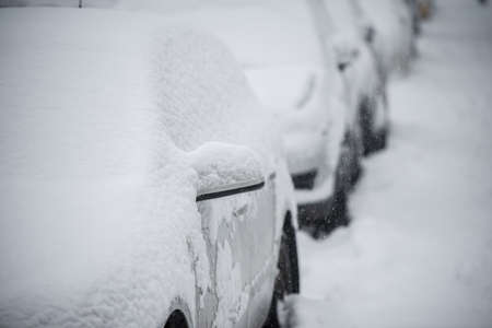 Parked cars covered with snow in winter blizzard