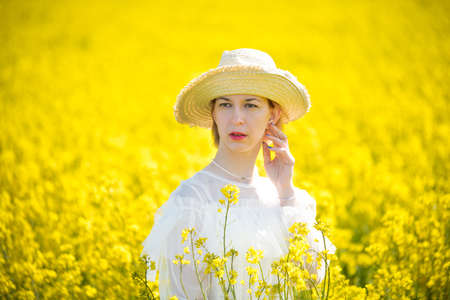 Young woman stands in a rape field