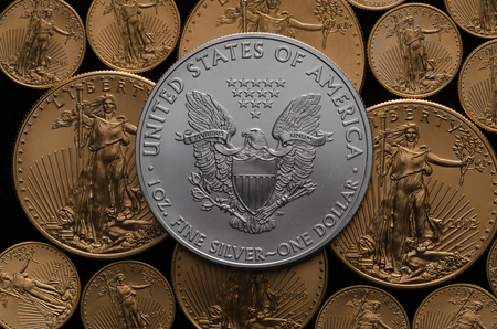 silver background: United States Silver Eagle Coin on bed of American Gold Eagles Stock Photo