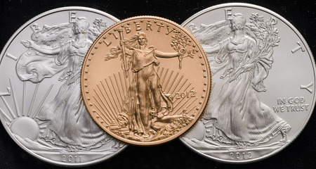gold silver: US Gold Eagle on 2 US Silver Eagles w Black background