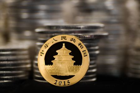 legal tender: This Chinese Gold Coin has piles of Silver Coins in the background.