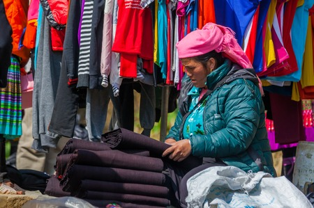 SA PA - DECEMBER 10, 2016: Street scene with local Hmong and Dao people comming and selling goods at sunday market on december 10, 2016 in Sa Pa, Vietnam.