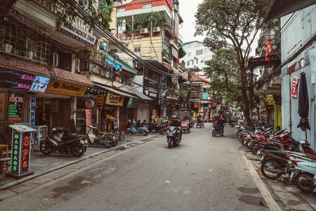 HANOI, VIETNAM - DECEMBER 14, 2018 : Street scene of the Old Quarter of Hanoi during the day. Lots of people and traffic in the narrow street.
