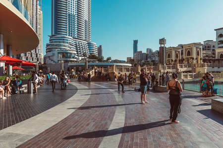 DUBAI, UAE - DECEMBER 12, 2018: Tourists and local people near Mall of Dubai. Tourist attracting Burj Khalifa. Busy tourist attraction area. Travel vacation concept