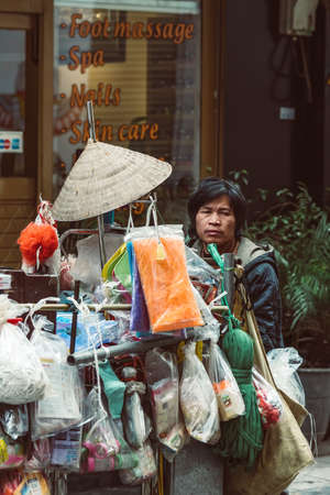 HANOI, VIETNAM - DECEMBER 15, 2018 : Street scene of the Old Quarter of Hanoi. Street vendor selling various types of traditional vietnamese hats from the bicycle