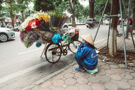 HANOI, VIETNAM - DECEMBER 14, 2018 : Local daily life of the morning street market, street vendors selling various types of flowers from their bicycle Editöryel