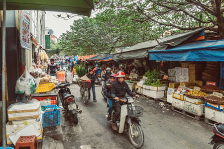 HANOI, VIETNAM - DECEMBER 14, 2018 : Street scene of the Old Quarter of Hanoi. Local daily life of the morning street market, street vendors selling various types of fruits and vegetables