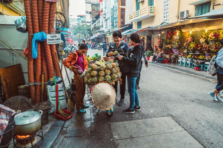 HANOI, VIETNAM - DECEMBER 14, 2018 : Street scene of the Old Quarter of Hanoi. Local daily life of the morning street market, street vendor selling various types of fruits from the bicycle